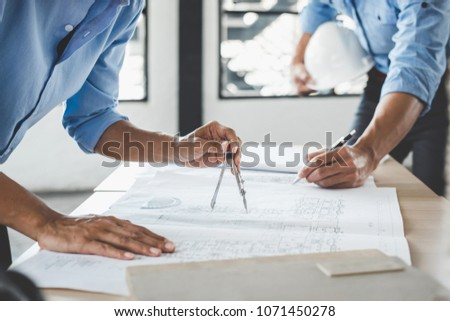 Construction concept of Engineer or architect meeting for project working with partner and engineering tools on model building and blueprint in working site. #1071450278