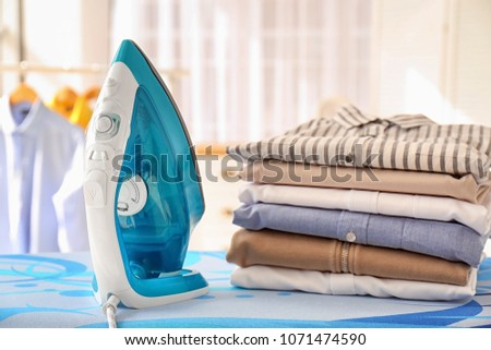 Stack of clean clothes and iron on board indoors #1071474590