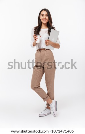 Full length portrait of a smiling asian businesswoman carrying laptop computer and cup of coffee to go while standing isolated over white background #1071491405