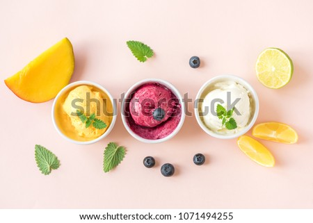 Three various fruit and berries ice creams on pink background, copy space. Frozen yogurt or ice cream with lemon, mango, blueberries - healthy summer dessert. #1071494255