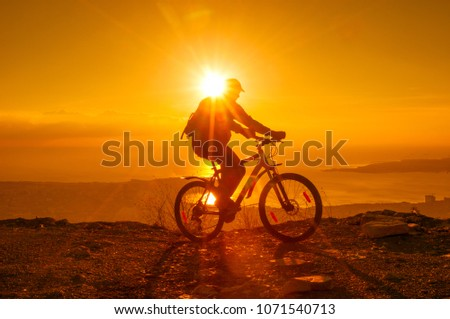 Silhouette of cyclist riding on a bike in mountain at sunset #1071540713