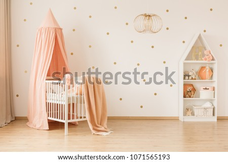 Gold lamp in spacious baby's bedroom interior with canopied pink crib against wallpaper #1071565193