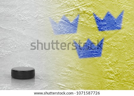 Hockey puck and the image of the Swedish flag on the ice. Concept, hockey
