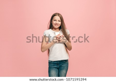 Happy teen girl standing, smiling isolated on trendy pink studio background. Beautiful female half-length portrait. Young satisfy girl with phone.  #1071595394