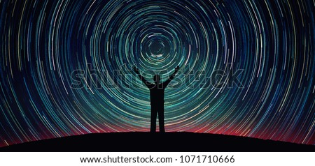 Man silhouette on a night sky background with bright stars trails. Man watching the stars. Science, education and religion team concept background. Elements of this image furnished by NASA. Royalty-Free Stock Photo #1071710666
