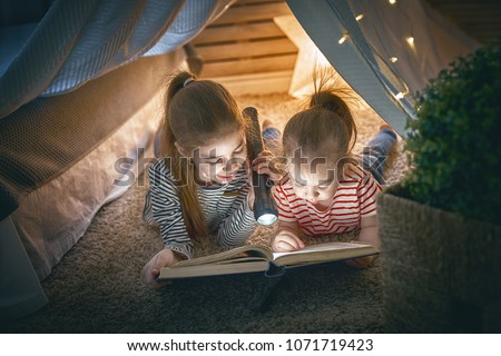 Two cute little children are reading a book with flashlights in tent. Happy girls playing at home. Funny lovely kids having fun in room.  #1071719423