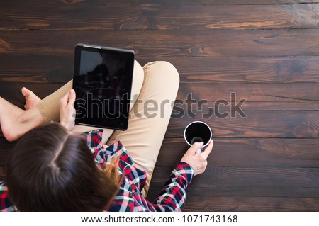the girl sits on a wooden brown floor with a cup of coffee in her hands, looks at the tablet, reads news and messages on the tablet, the top view #1071743168