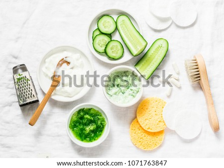 Calming cucumber yogurt mask. Ingredients for homemade cucumber face mask-cucumber, natural yogurt, probiotic capsule, sponges, brush on white background, top view. Flat lay #1071763847