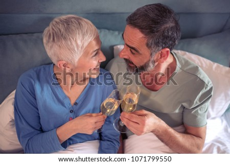 Portrait of a happy mature couple with wine glasses in their bedroom. #1071799550