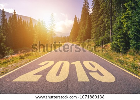 Empty asphalt road and New year 2019 concept. Driving on an empty road in the mountains to upcoming 2019 and leaving behind old 2018. Concept for success and passing time. #1071880136