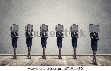 Businessmen in suits with old TV instead of their heads keeping arms crossed while standing in a row and one at the head with TV in empty room against gray wall on background. #1071911450