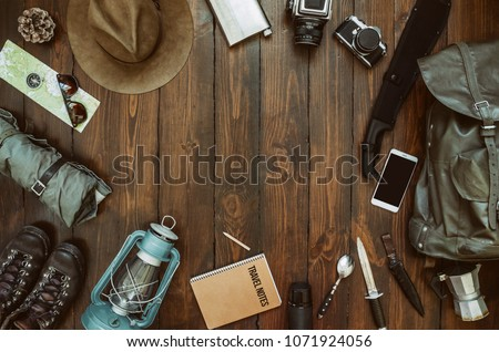 Hiking gear frame including backpack machete, knife, clothes, boots, lantern, camera, hat, map, compass. Packing for a hike concept. Wanderlust, safari equipment postcard, poster, banner background. #1071924056