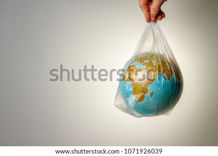 The concept of World Environment Day. The man's hand holds the earth in a plastic bag. In the blank for social advertising there is a place for the inscription. #1071926039