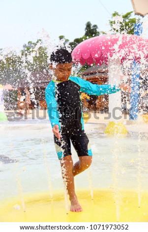 A boy wearing a swimsuit is playing splashing water. #1071973052