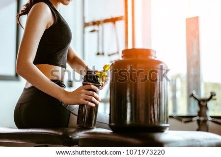 Relaxing after training.beautiful young woman looking away while sitting  at gym.young female at gym taking a break from workout.woman brewing protein shake. #1071973220