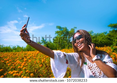 happy and beautiful young Asian tourist woman taking selfie pic in gorgeous orange marigold flowers field natural landscape in travel destination and holidays Summer trip tropical excursion