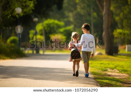 Brother and sister walk through the Park #1072056290
