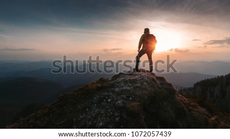 Tourist man hiker on top of the mountain. Active life concept Royalty-Free Stock Photo #1072057439