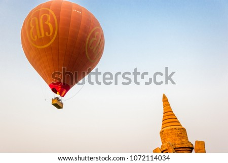 Bagan, Myanmar - 11, March 2018, hot air balloon flying at sunrise over the temples of Old Bagan.. Ballooning over Bagan adventure activity for tourists. #1072114034