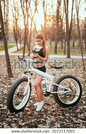 brunette with headphones is printing on phone and holding bicycle at sunset in park