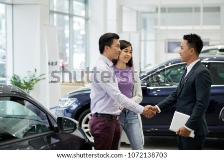 Vietnamese couple buying new automobile #1072138703