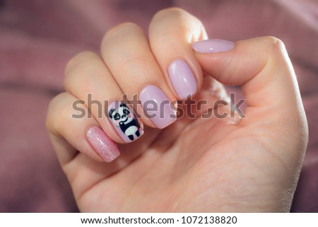 The nail is decorated with a picture of a charming panda with a gesture of greeting. Lacquer on a nail of pastel pink, lilac color with glitters. Spring caramel color palette.