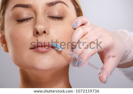 Young woman with syringe in cosmetologist's hand. Beauty injection's concept #1072159736