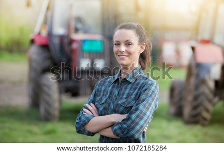 Young pretty farmer woman standing on farmland with crossed arms and tractors in background #1072185284