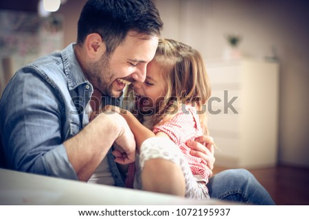 Father and daughter playing together at home. Royalty-Free Stock Photo #1072195937