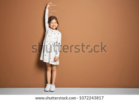 Little girl measuring her height near color wall #1072243817