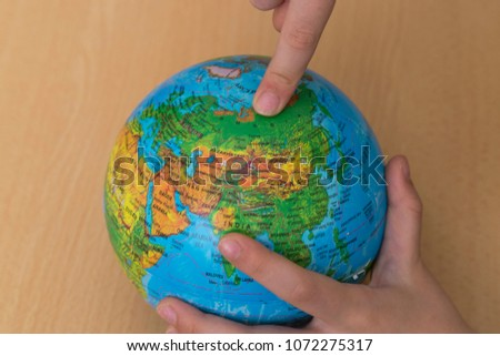sphere on the map of the world.someone shows Russia on the map. we teach children the world. #1072275317