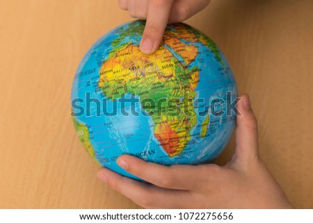 sphere on the map of the world.someone shows Africa on the map. we teach children the world. #1072275656