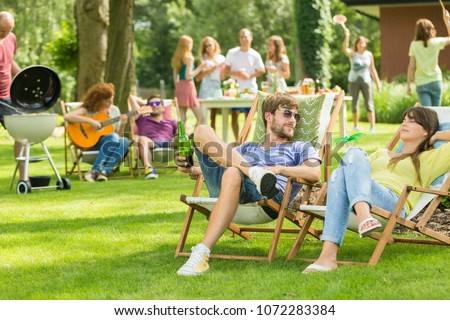 Young friends having barbecue picnic in the nature, playing guitar, playing badminton, enjoying sunny summer day outdoor #1072283384