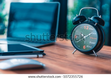 Focus on clock near laptop and computer put on woking table #1072355726