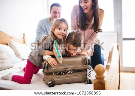 Young family with two children packing for holiday. Royalty-Free Stock Photo #1072358855
