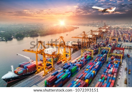 Logistics and transportation of Container Cargo ship and Cargo plane with working crane bridge in shipyard at sunrise, logistic import export and transport industry background #1072393151