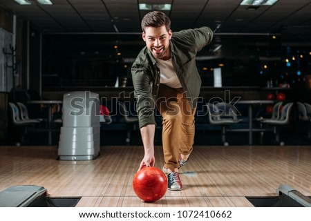 happy young man throwing bowling ball and looking at camera