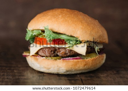 fresh tasty burger on wooden table #1072479614