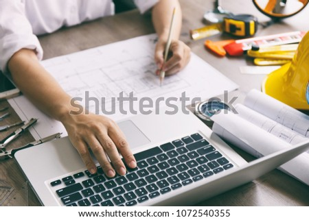 Architect hands working on blueprint plans  with  a pencil,  a ruler, calculator, smartphone, laptop and engineering tools #1072540355