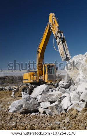 Hydraulic breaker hammer destroys a large stone against the background of a blue sky, close-up, front view. Heavy equipment. Mining industry. #1072545170