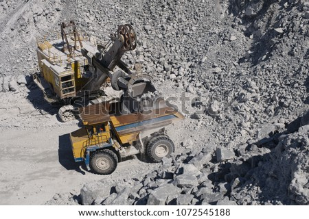 Heavy mining excavator loads rock ore into a heavy dump truck in a limestone quarry, close-up, top view. Heavy equipment. Mining industry. #1072545188