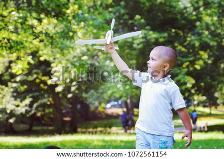 happy boy play and  throw airplane in park #1072561154