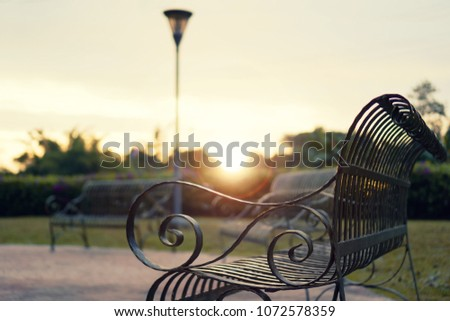 Black iron bench in the city park during sunset #1072578359