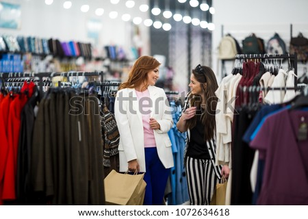 Two happy women shopping in retail store. Friends choosing clothes  in store. #1072634618