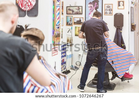 Ufa, Russia. 16 April 2018: Men's haircut in barber shop. Master at work. Interior and workflow #1072646267