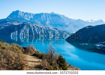 A view of the mountains near lake Lac de serre-poncon in French Alps on a clear day #1072710332