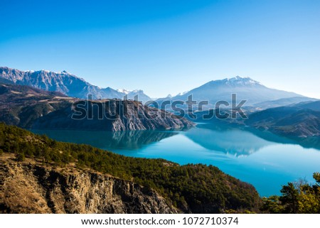 A view of the mountains near lake Lac de serre-poncon in French Alps on a clear day #1072710374