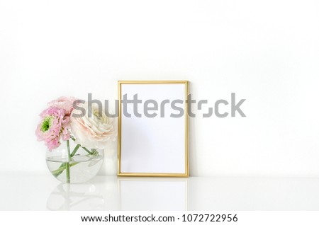 Ranunculus in a vase with a frame for the presentation of works and accessories. Everything is on the table in the interior.Mock-up for displaying works.