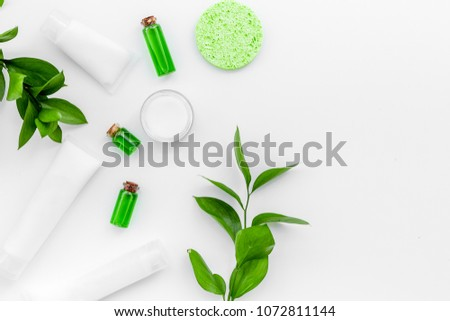 Natural cosmetics for skin care near green leaves on white background top view copy space #1072811144