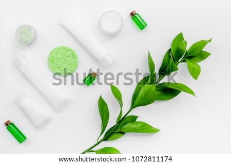 Natural cosmetics for skin care near green leaves on white background top view #1072811174